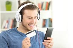 Individuo que paga fluyendo música con la tarjeta de crédito Foto de archivo libre de regalías