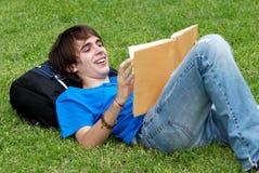 Individuo que pone en la hierba y que lee un libro Imagen de archivo libre de regalías