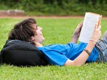 Individuo que pone en la hierba y que lee un libro Imágenes de archivo libres de regalías