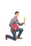 Individuo que se agacha abajo en su rodilla con un manojo de tulipanes Foto de archivo