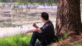 Individuo que se relaja cerca de un lago almacen de video