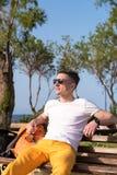 Individuo que se sienta en un banco cerca del mar Imagenes de archivo