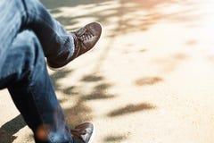 Individuo que se sienta en un banco en zapatillas de deporte y tejanos negros Foto de archivo libre de regalías