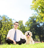 Individuo que se sienta en una hierba al lado de su perro del labrador retriever en un p Imagen de archivo