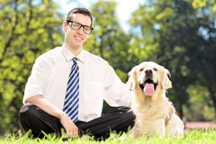 Individuo que se sienta en una hierba verde al lado de su perro en parque Foto de archivo