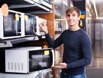 Individuo que selecciona el horno de microondas Imagen de archivo