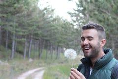 Individuo que sonríe alrededor para soplar en el diente de león blanco en el bosque con el espacio de la copia imagen de archivo
