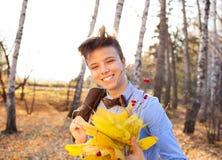 Individuo que sostiene el ramo de hojas de otoño Foto de archivo libre de regalías