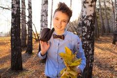 Individuo que sostiene el ramo de hojas de otoño Foto de archivo