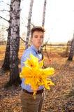 Individuo que sostiene el ramo de hojas de otoño Imagen de archivo