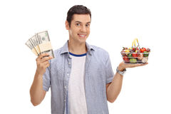 Individuo que sostiene pilas del dinero y la cesta de compras Imagen de archivo