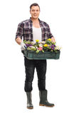 Individuo que sostiene un cajón plástico con las flores en él Foto de archivo libre de regalías