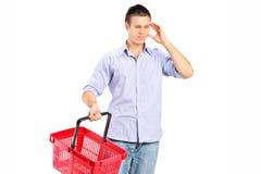 Individuo que sostiene una cesta de compras vacía Imagen de archivo libre de regalías