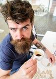 Individuo que tiene resto con café del café express Inconformista en el café de consumición de la cara estricta seria al aire lib Foto de archivo