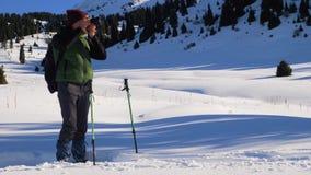 Individuo que tira una foto del paisaje de la montaña en invierno metrajes