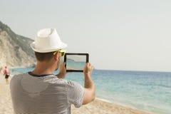 Individuo que toma una foto de una playa con su dispositivo digital de la tableta Imagen de archivo libre de regalías