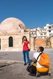 Individuo que toma una imagen de la muchacha delante de la catedral Foto de archivo