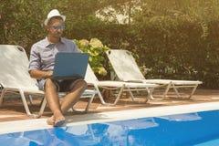 Individuo que trabaja en el ordenador portátil al lado de la piscina Foto de archivo