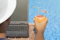 Individuo que trabaja en el ordenador portátil y que disfruta de sus vacaciones de verano imágenes de archivo libres de regalías