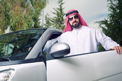 Individuo árabe que presenta contra su coche en casa Imagen de archivo