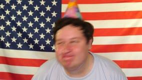 Individuo relajado alegre del cumpleaños con el sombrero del cono en su cabeza que ríe mientras que divirtiéndose, disfrutando de almacen de video