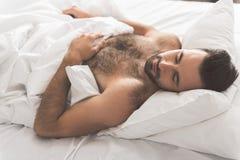 Individuo relajado que tiene siesta en el lecho blanco Fotos de archivo