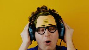 Individuo rizado cómico loco que escucha la música en auriculares o auriculares retros metrajes