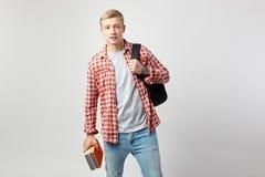 Individuo rubio joven con la mochila negra en su hombro vestido en una camiseta blanca, una camisa a cuadros roja y controles de  foto de archivo libre de regalías