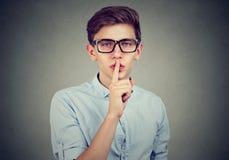 Individuo secreto Sirva decir que el silencio sea reservado con el finger en el gesto de los labios que mira la cámara Imágenes de archivo libres de regalías