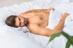 Individuo sereno que tiene siesta en cama Imagen de archivo libre de regalías