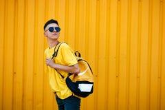 Individuo serio elegante en una camiseta amarilla sucia y gafas de sol y Foto de archivo
