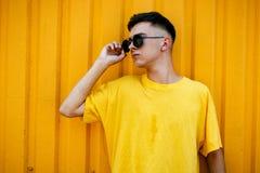 Individuo serio elegante en una camiseta amarilla sucia y gafas de sol Imagenes de archivo