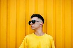 Individuo serio elegante en una camiseta amarilla sucia y gafas de sol Imágenes de archivo libres de regalías