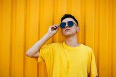 Individuo serio elegante en una camiseta amarilla sucia y gafas de sol Foto de archivo libre de regalías