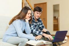 Individuo serio y muchacha que se preparan para el examen con el ordenador portátil Imagen de archivo libre de regalías