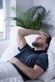 Individuo soñoliento con dolor de cabeza imagenes de archivo