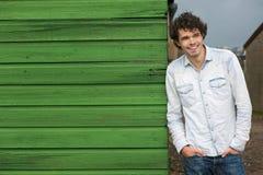 Individuo sonriente casual que se inclina contra la pared verde Imagenes de archivo