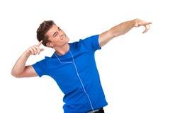 Individuo sonriente en música que escucha de los auriculares en el fondo blanco Imagenes de archivo