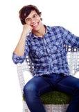 Individuo sonriente en silla con la mano debajo de la mejilla Imagen de archivo libre de regalías