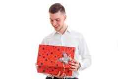 Individuo sonriente joven en la camisa blanca que sostiene un regalo rojo grande Foto de archivo libre de regalías