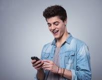 Individuo sonriente que manda un SMS con smartphone Imagen de archivo libre de regalías