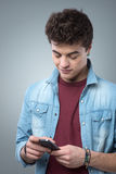 Individuo sonriente que manda un SMS con smartphone Foto de archivo libre de regalías