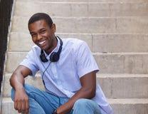 Individuo sonriente que se sienta en pasos afuera con los auriculares Imagenes de archivo