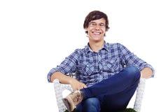 Individuo sonriente que se sienta en silla Imagenes de archivo