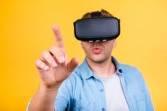 Individuo sorprendente en la camisa de los vaqueros que lleva gafas de la realidad virtual, usando Foto de archivo libre de regalías