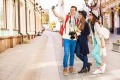 Individuo y dos muchachas que toman selfies con el teléfono móvil Foto de archivo libre de regalías