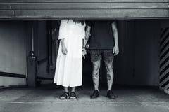 Individuo y muchacha detrás del obturador del rodillo Foto de archivo