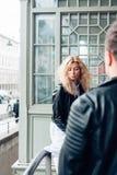 Individuo y muchacha en chaquetas negras en una calle de la ciudad Imagenes de archivo