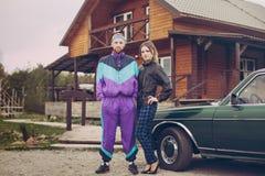 Individuo y muchacha en la ropa de los años noventa, al lado del coche viejo Imagenes de archivo