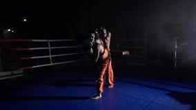Individuo y muchacha en los cascos y los guantes de boxeo a luchar en el anillo Cámara lenta almacen de metraje de vídeo